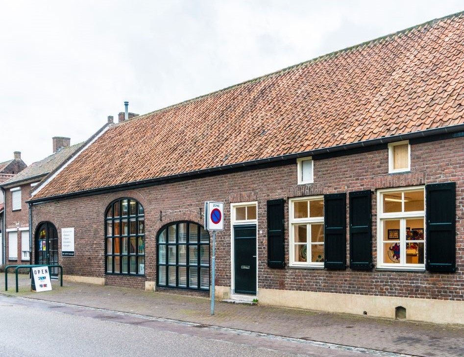 Voorgevel van Atelier27 Driessensstraat 27 in Neeritter met expo bord buiten en licht aan in het atelier ruimte