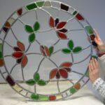 Glas in lood met rode bloemen en groene bladeren met veel transparant glasn blauwtinten