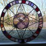 Glas in lood paneel in paars tinten tegen raam