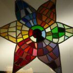 Zespuntige ster glas in lood paneel met in iedere punt een andere kleur, geel, blauw, oranje, groen, paars en rood